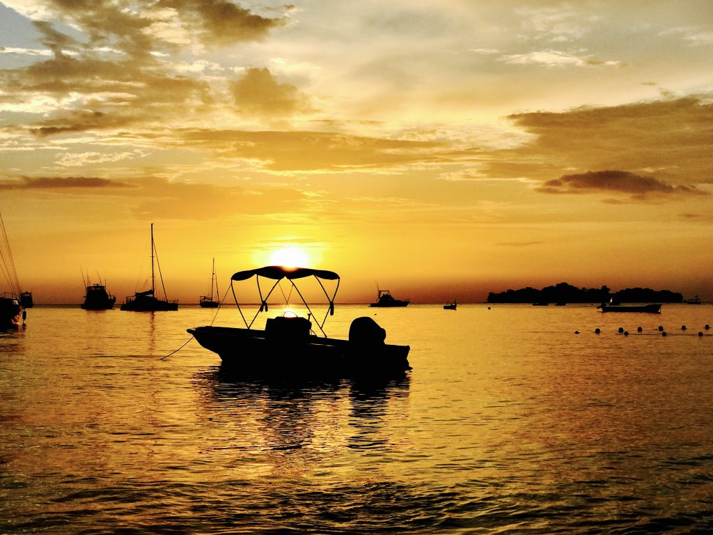 Photo of the sunset over the ocean with a small motor boat silhouetted in the foreground.
